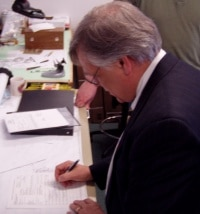 Joseph d'Entremont,  Lenox Laser President, signs NASA flight certifications